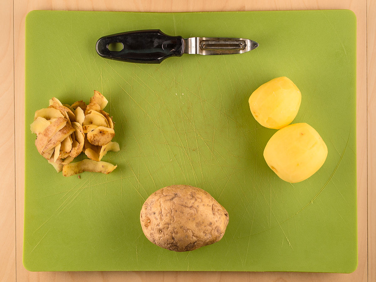 An old fashioned potato peeler on a cutting board with some potatoes in various states of peeling.