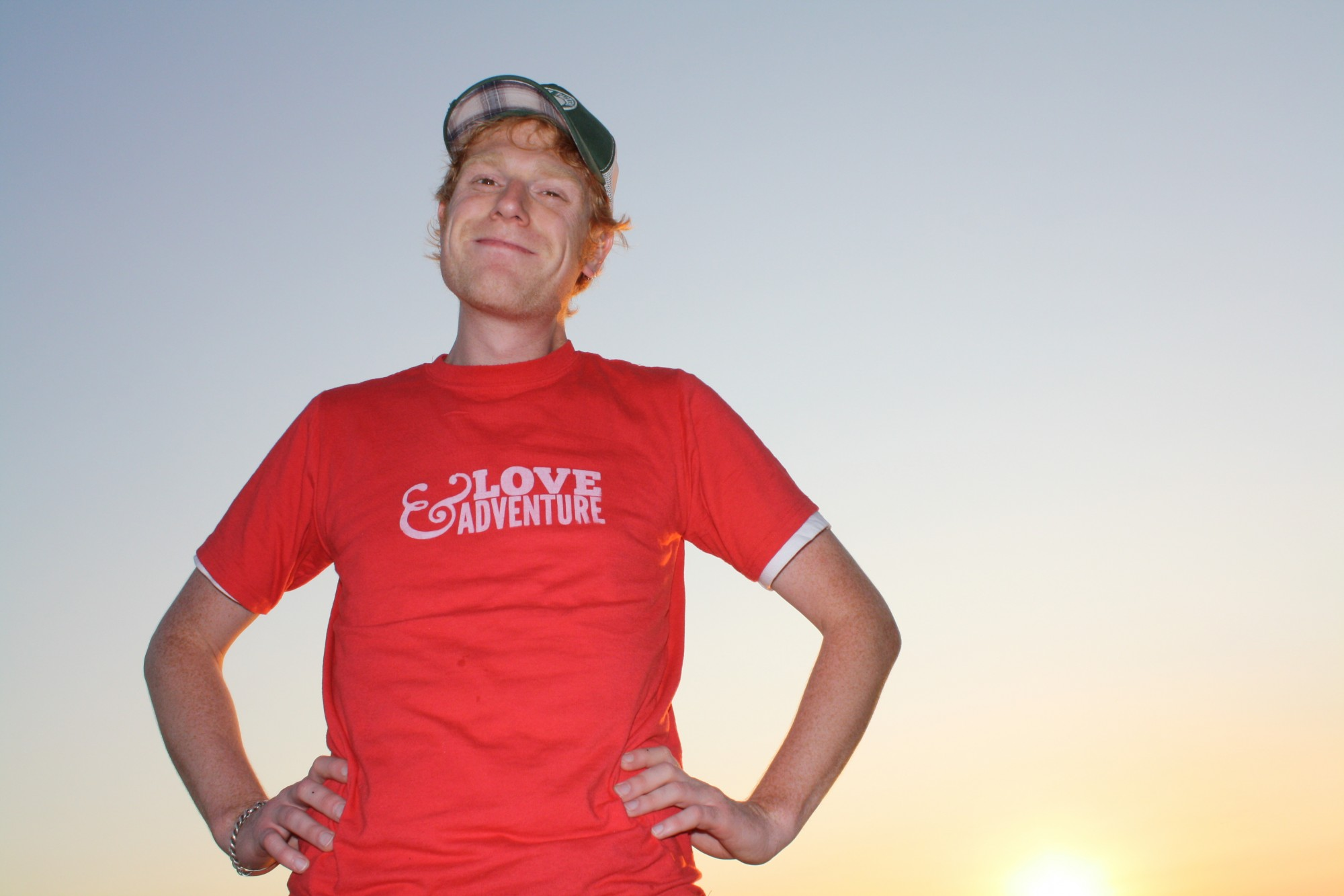 Ryan Bender of Love & Adventure standing in front of a sunset on a lake
