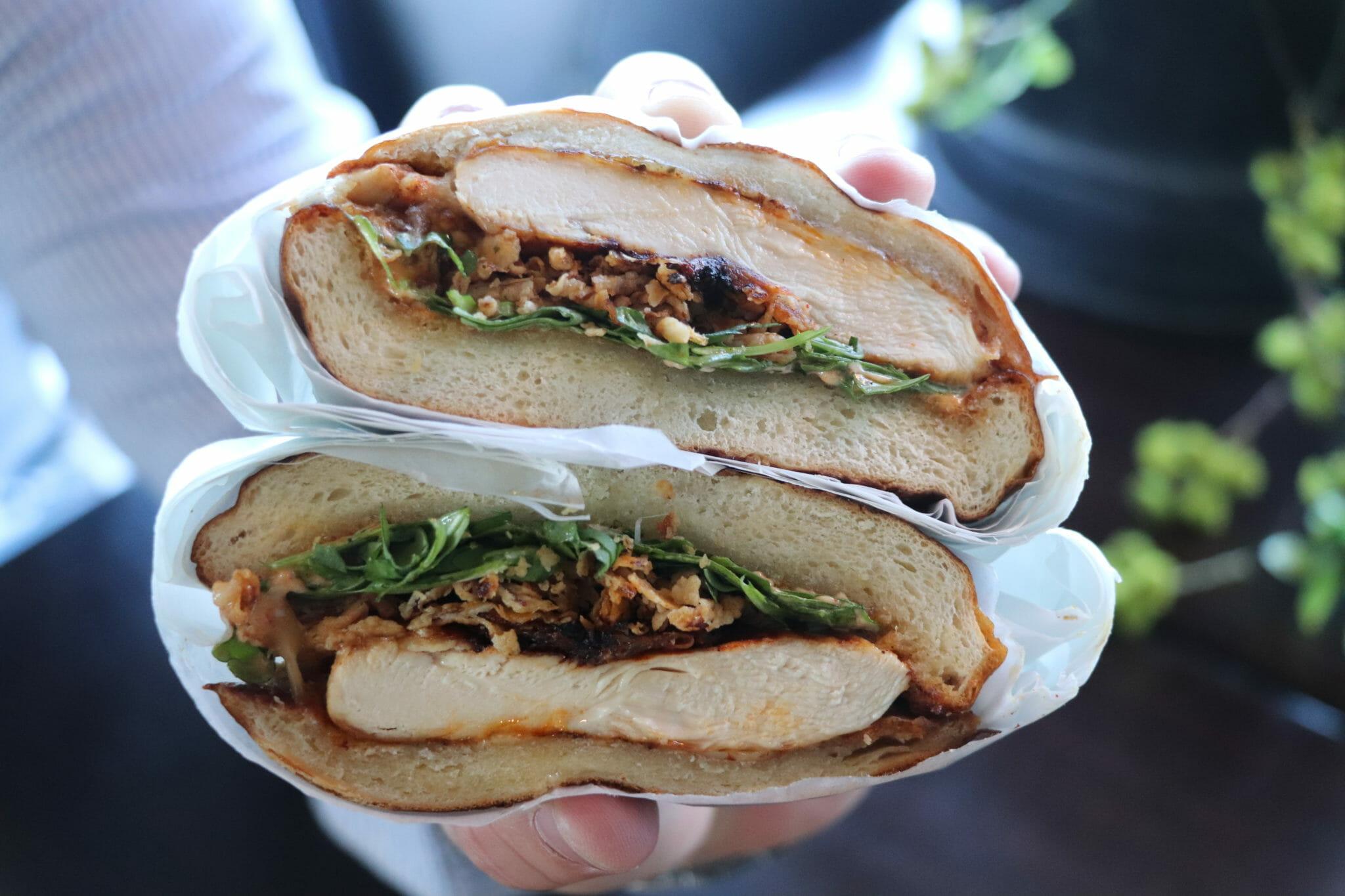 Hand holding spiced chicken sandwich