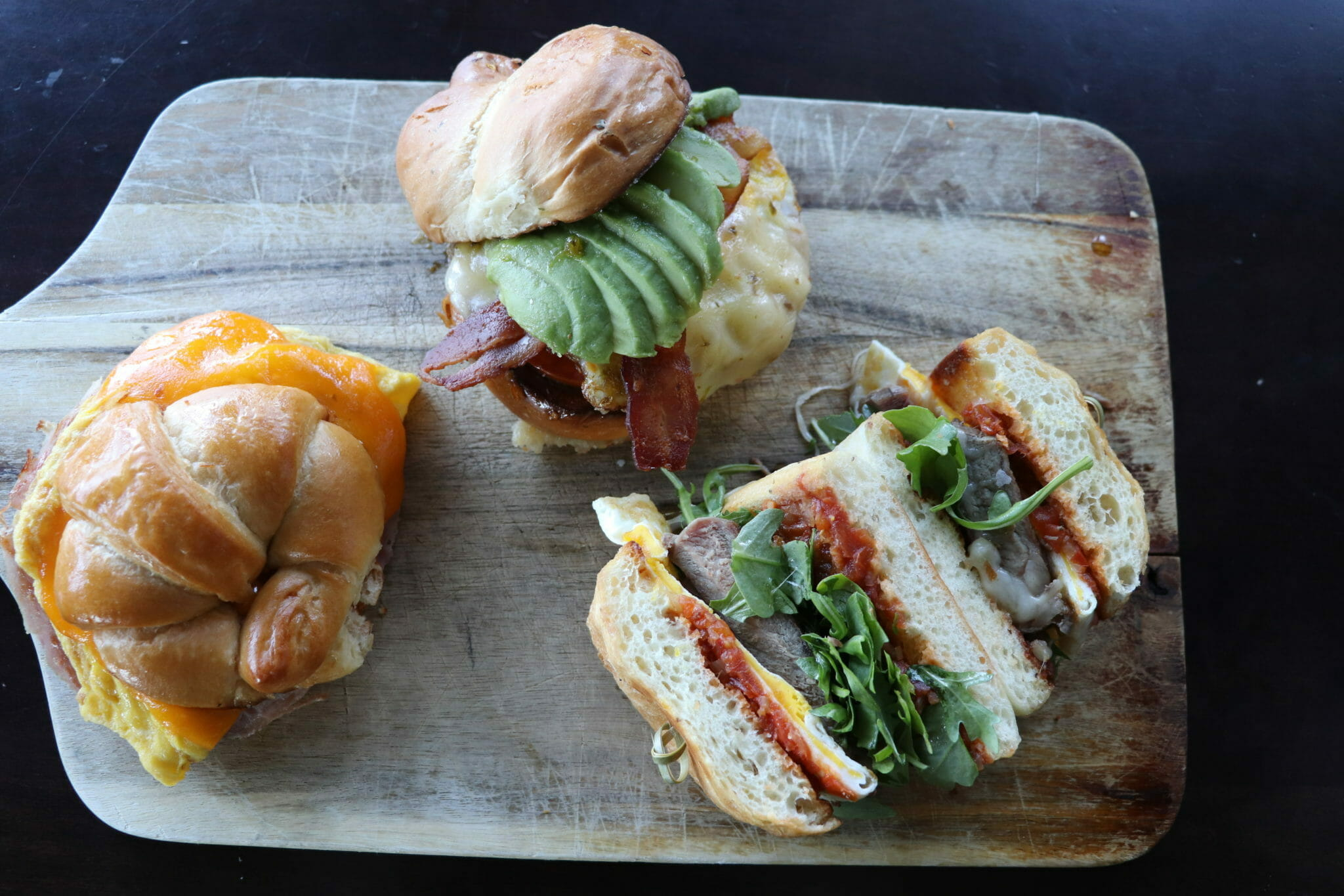 Three breakfast sandwiches on cutting board