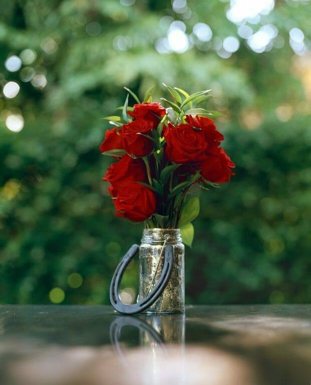 Vase of flowers on table with horseshoe