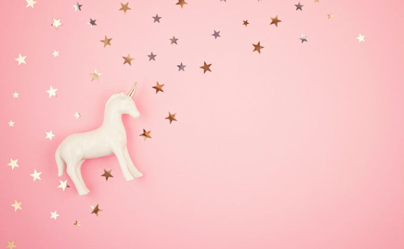 Flat lay with white unicorn and stars over the pink background