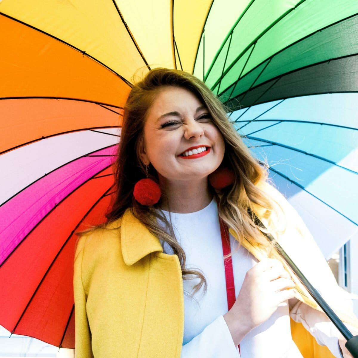 Allie holding a rainbow umbrella