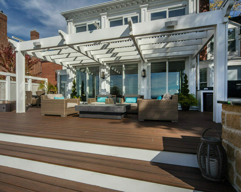 Custom designed exterior deck remodel with spa, cooking space, counter seating, dining area, and lounge area under a pergola overlooking Lake Mendota, by TDS Custom Construction.