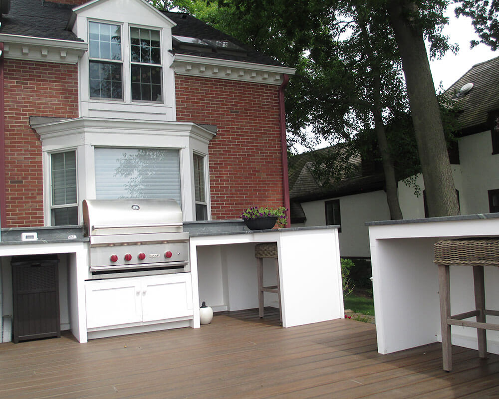 An exterior deck remodel transforms a stone patio into an impressive deck that includes a spa, cooking space, counter seating, dining area, and lounge area under the pergola.