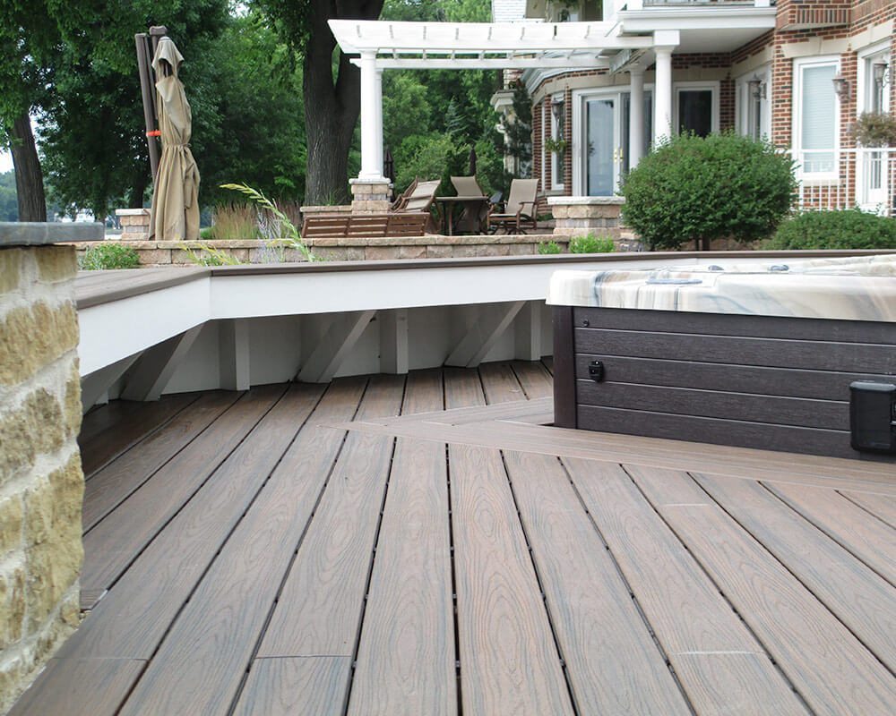 Former stone patio was converted into an impressive exterior deck remodel and addition that matches the style of the home and creates an entertainment area overlooking Lake Mendota, by TDS Custom Construction.