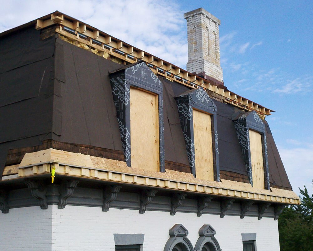 Process photograph of the historic restoration of a 1880's Second Empire Victorian home in Portage, WI. Here the dormers are being restored.