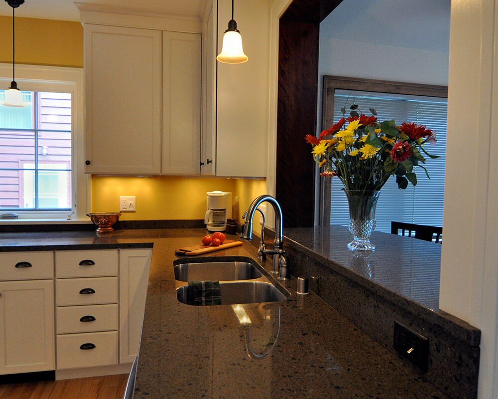 View from the kitchen of the breakfast bar. Custom design/build kitchen remodel for a more efficient kitchen with plenty of storage, multiple work zones, and butcher block countertops by TDS Custom Construction.