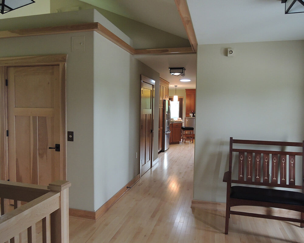 Wide hallways and a residential elevator in this entryway designed for aging in place by TDS Custom Construction.