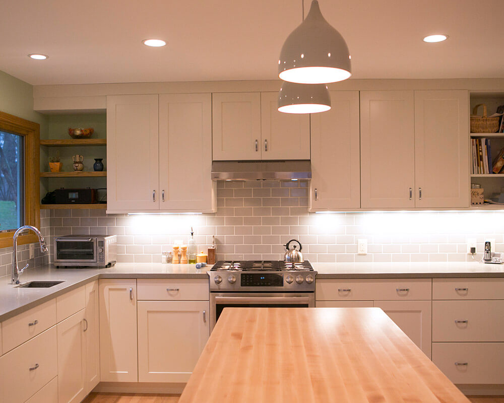 Midcentury modern inspired kitchen remodel with contemporary finishes like butcher block counters, subway tile back splash, and retro lighting by TDS Custom Construction.