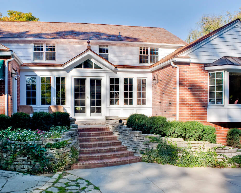 Exterior view of a home addition of a sunroom adds indoor-outdoor space to the rear of a traditional home in Madison.