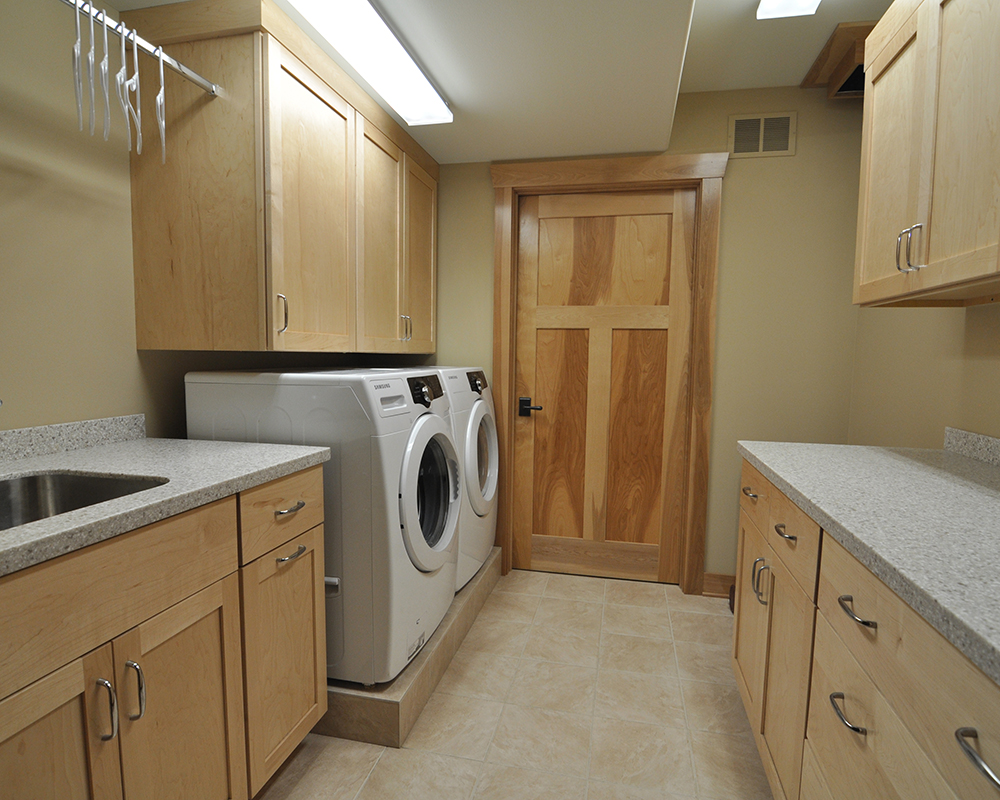 Universally designed basement laundry room with custom cabinets by TDS Custom Construction.