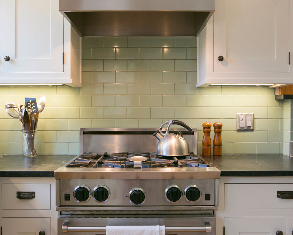 Kitchen remodel with custom Woodharbor inset cabinets and BlueStar range, and celadon subway tile backsplash by TDS Custom Construction in Madison, WI