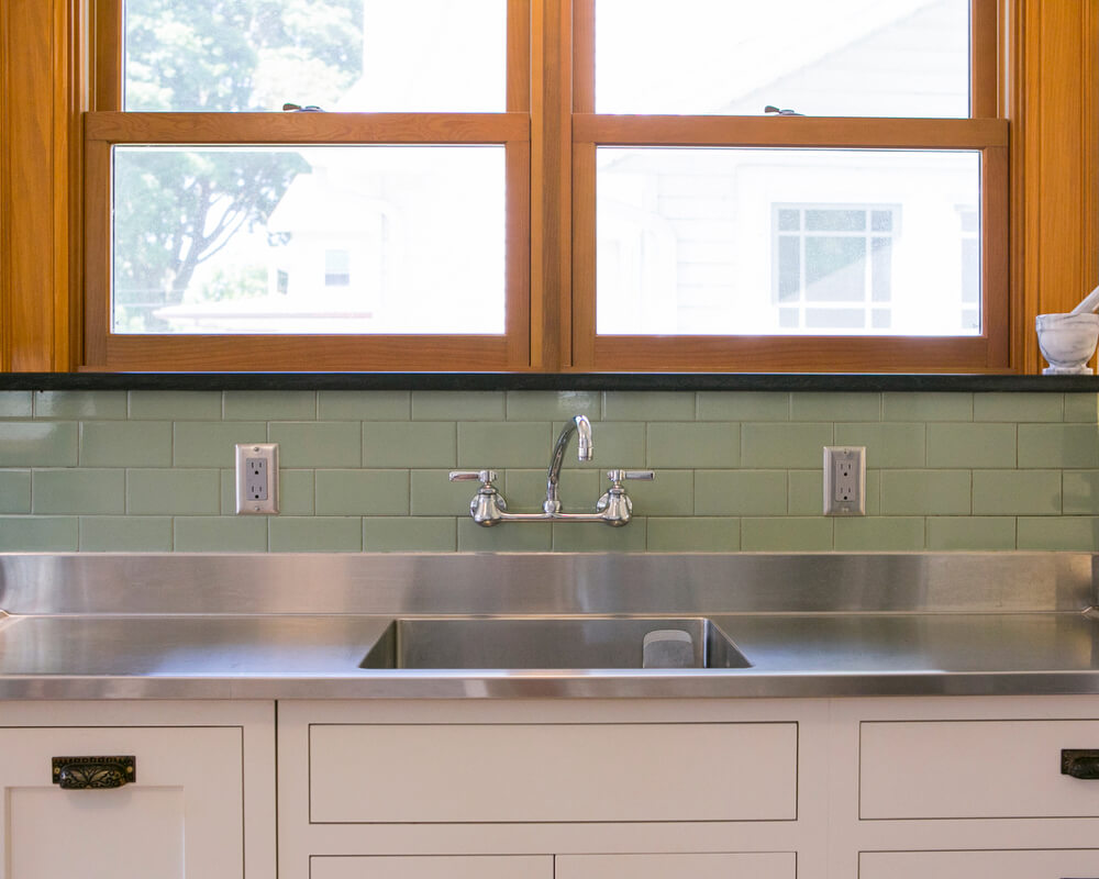 Kitchen remodel with local granite countertop and window ledge, custom stainless steel sink, and wall-mounted faucet by TDS Custom Construction in Madison, WI