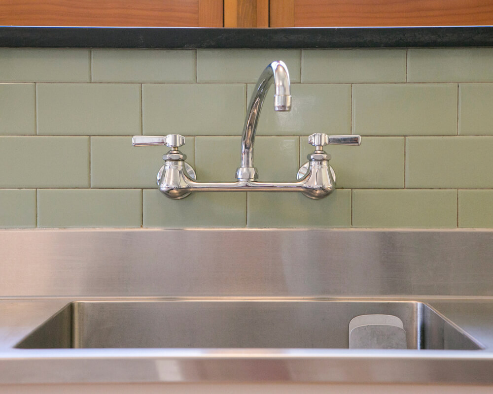Kitchen remodel with custom stainless steel sink and wall-mounted faucet by TDS Custom Construction in Madison, WI