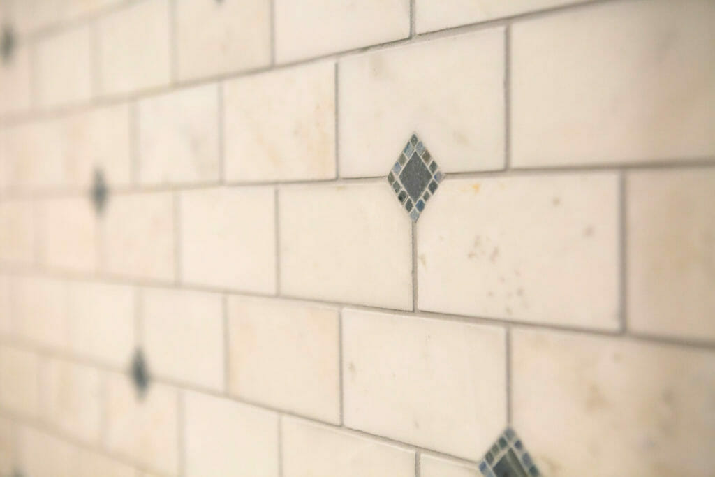 Bathrooms were updated with natural stone tile and mosaic inlays in Maple Bluff, WI by TDS Custom Construction.