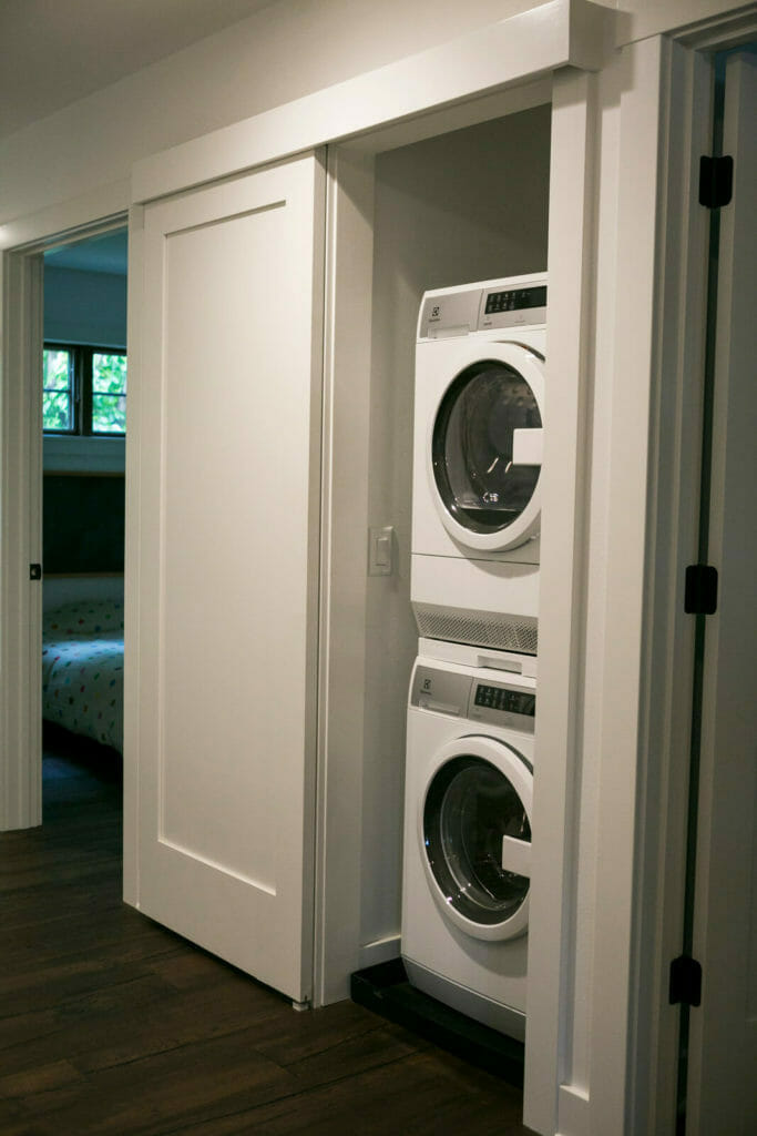 A stacked washer and dryer and a sliding door optimize the space in this 1,000 square foot modern whole house remodel in Monona, Wisconsin by TDS Custom Construction.