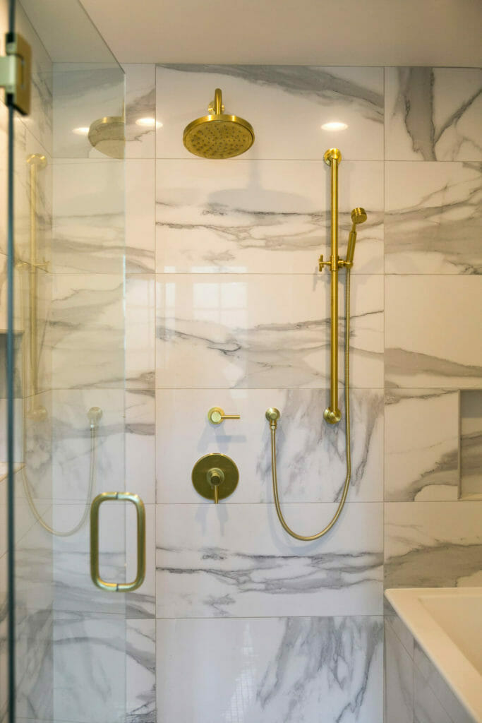 Marble shower and bath with modern brass faucets for this bathroom remodel in Maple Bluff, Wisconsin by TDS Custom Construction.