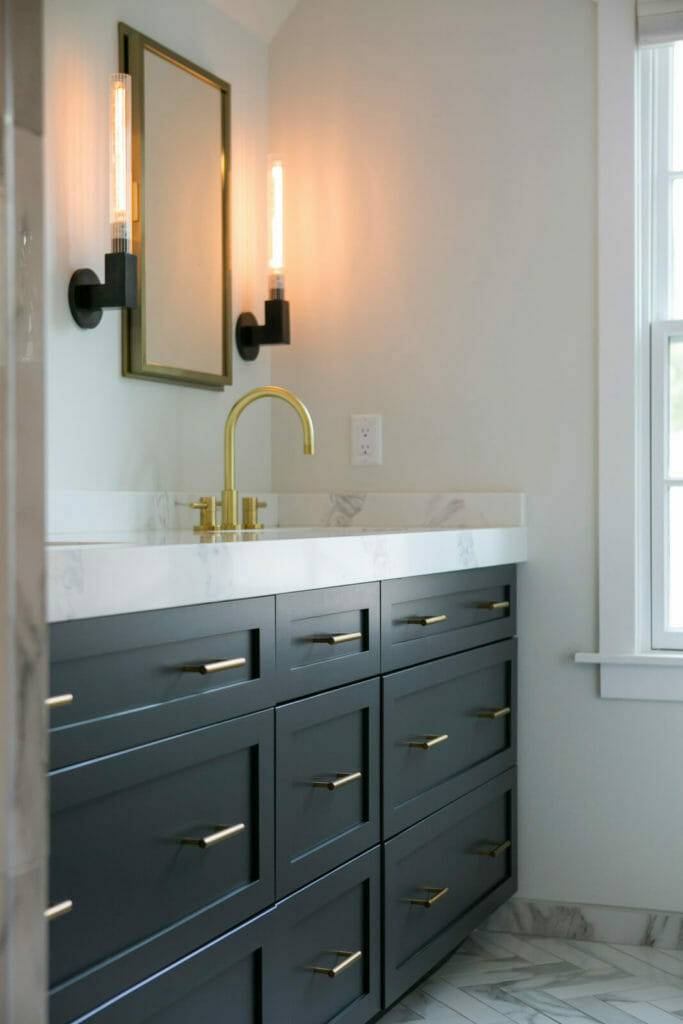 Ensuite bathroom remodel with brass fixtures, marble tiled shower and bathtub, painted Woodharbor cabinets, and marble tile in Maple Bluff, Wisconsin by TDS Custom Construction.