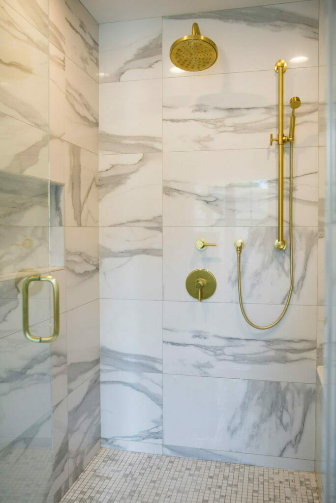 Marble shower with modern brass faucets for this bathroom remodel in Maple Bluff, Wisconsin by TDS Custom Construction.