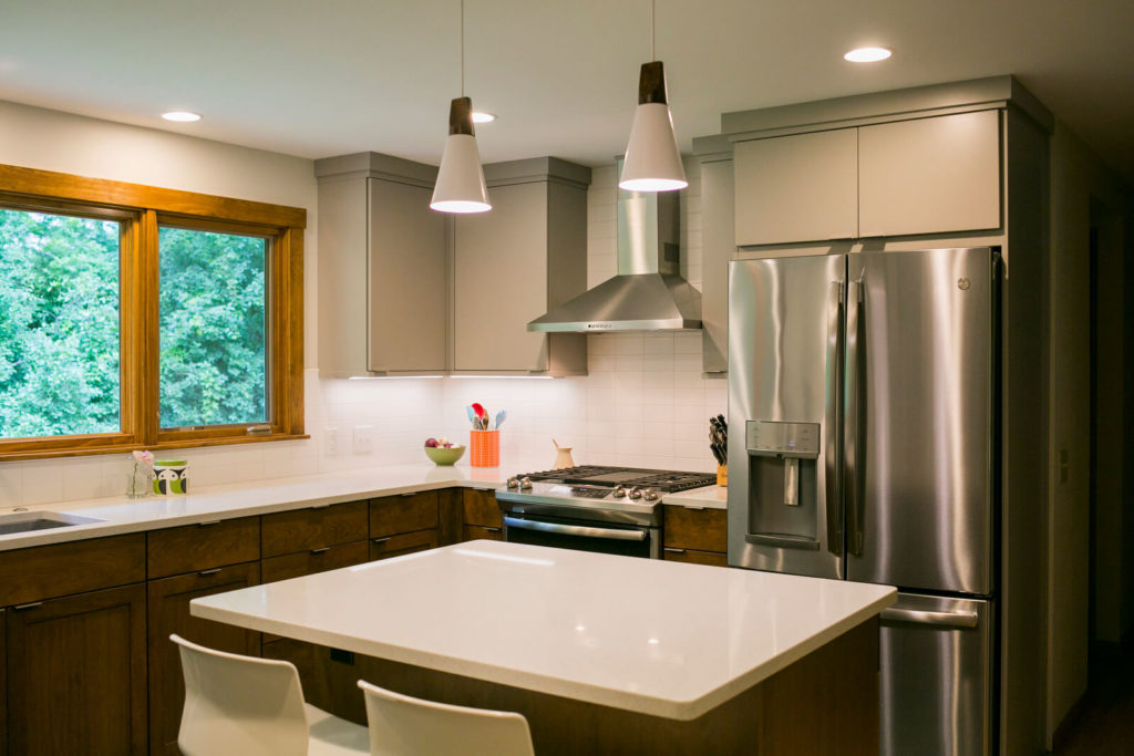 Quartz countertops, stainless steel appliances, Woodharbor painted and walnut cabinets, with modern accents, create a fresh kitchen remodel by TDS Custom Construction.
