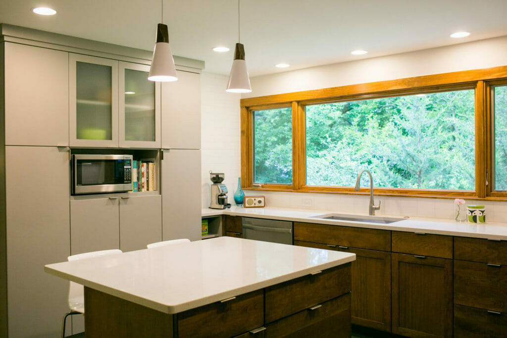 Quartz countertops, Woodharbor painted and walnut cabinets, with modern accents, create a fresh kitchen remodel by TDS Custom Construction.