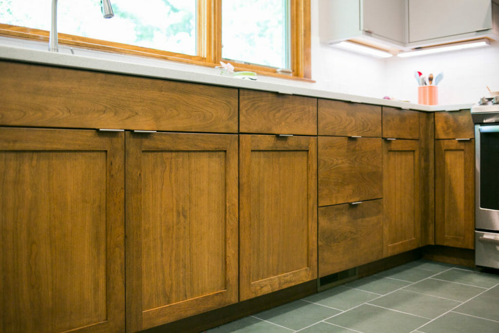 Woodharbor walnut lower cabinets and painted upper cabinets installed in a near-west Madison Wisconsin kitchen remodel by TDS Custom Construction.