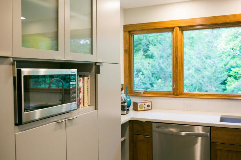 Near-west kitchen remodel with walnut and painted WoodHarbor cabinets and quartz countertops for a nearwest-side Madison home. A design/build kitchen remodel by TDS Custom Construction.