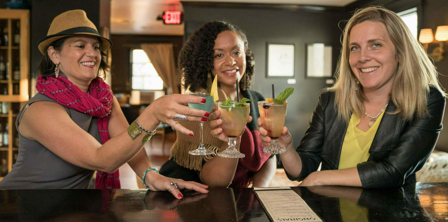 Women toasting cocktail glasses at bar