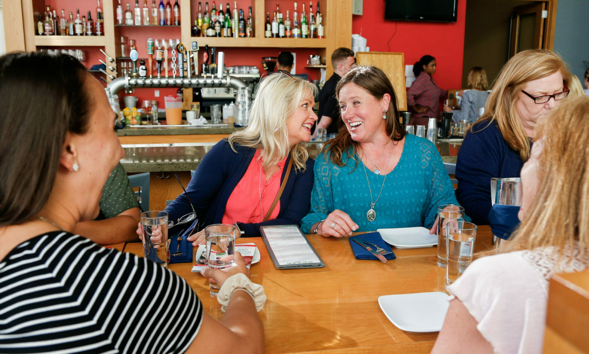 Guests laughing at restaurant dining table