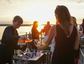 Serving pouring rose wine at sunset for guests