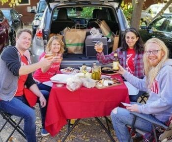 Group tailgating with table spread of food