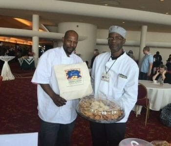 Two caterers holding tray of food at Monona Terrace event