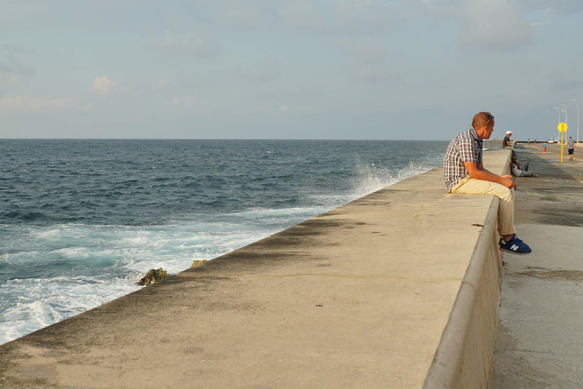 Man sitting by ocean's edge