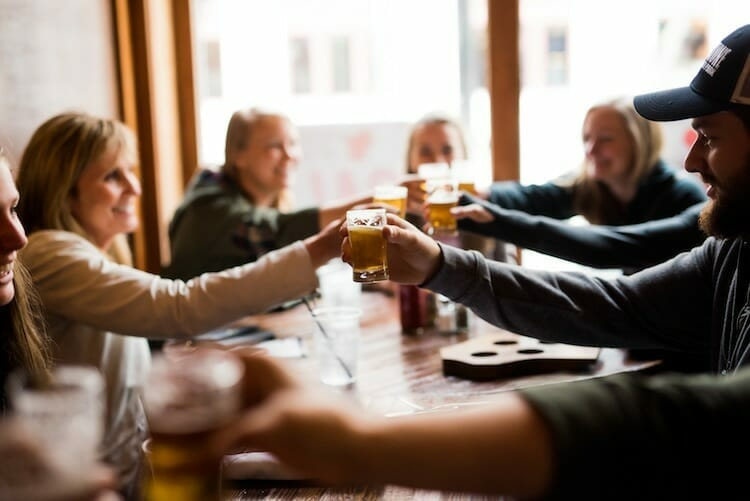Guests toasting glasses of craft beer on Around the Square food and drink tour