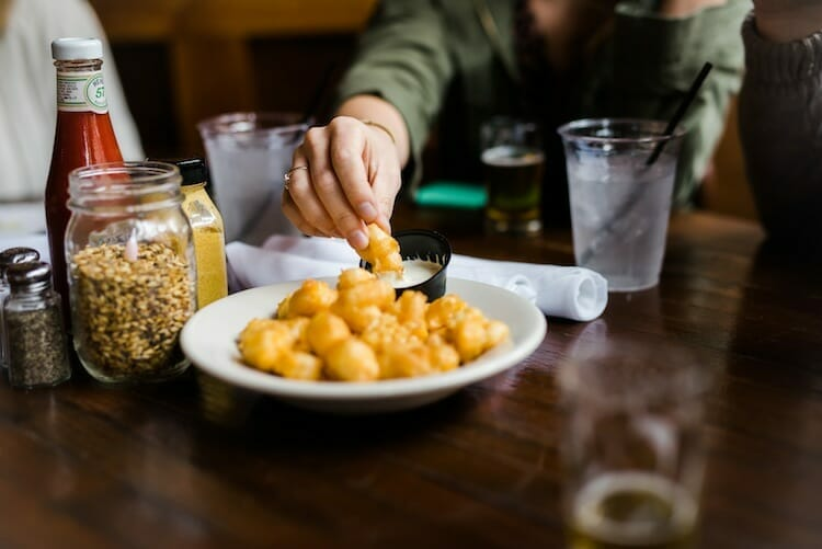 Guest dipping cheese curds on food tour