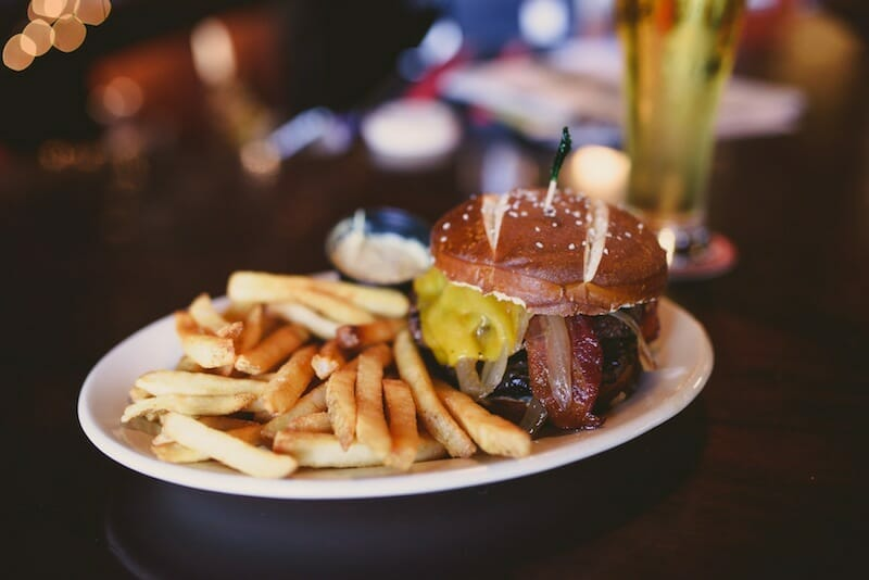 Plate of pretzel bun burger and fries from Around the Square food tour