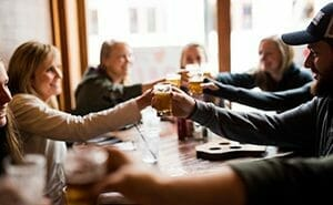 Guests toasting glasses of craft beer from Around the Square food and drink tour