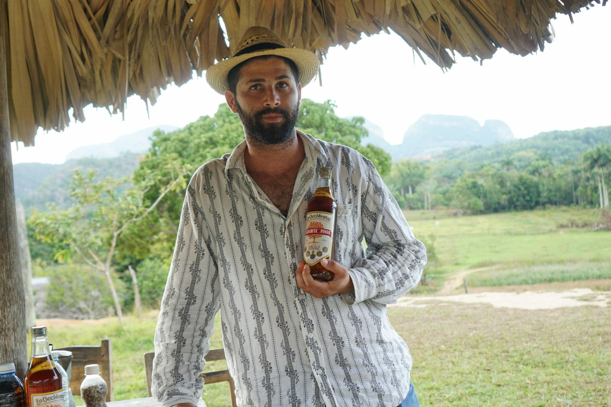 Farmer holds locally produced rum in Viñales, Cuba