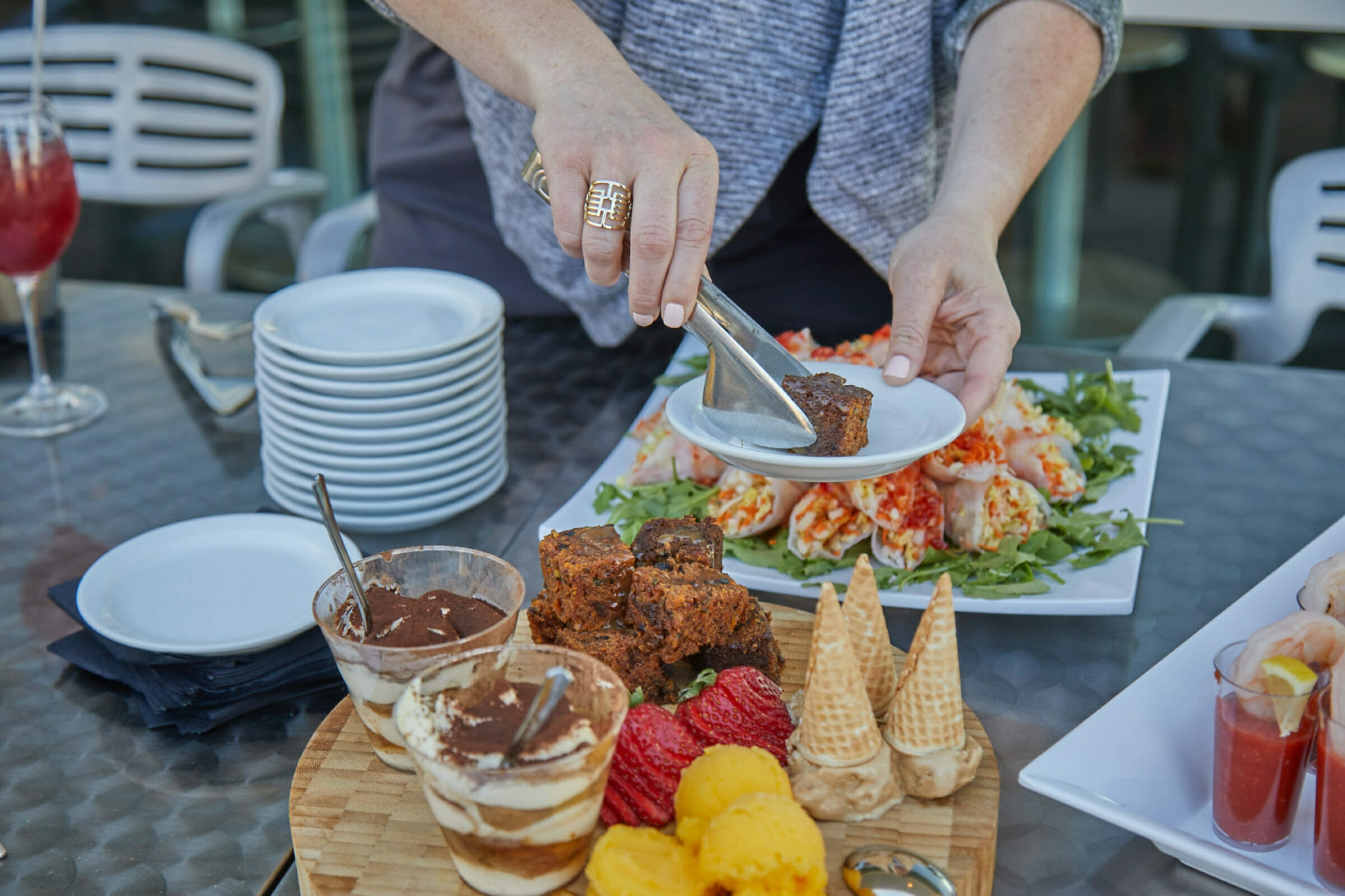 Woman dishing up plate at table of desserts & appetizers from Fare & Square food tour