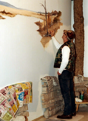 Artist Andy Stoffel works on the wetland mural